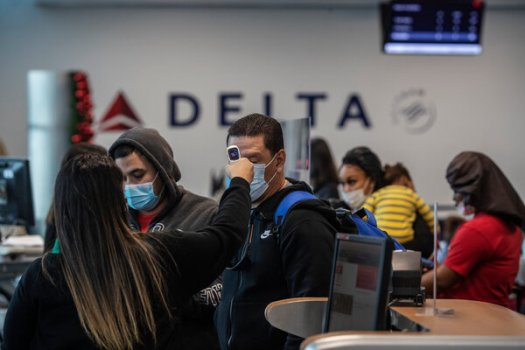 Passengers received temperature checks before boarding their flight at La Guardia Airport in New York on Monday.