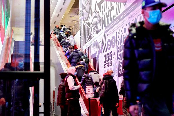 Black Friday shoppers rush inside a FootLocker store in Manhattan.