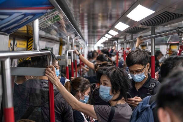 Travelers on the subway in Hong Kong this month. The city is seeing another surge in Covid-19 cases.