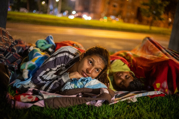 Jessika Loaiza and Sebastián, her son, before going to sleep on the street in Bogotá. The Times followed them to help readers understand the experience of millions of migrants like them.