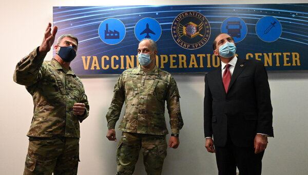 Gen. Gustave F. Perna, center, the chief operating officer of Operation Warp Speed, and Alex M. Azar II, right, the secretary of health and human services, received a tour of the vaccine operation center at the H.H.S. headquarters in Washington on Saturday.
