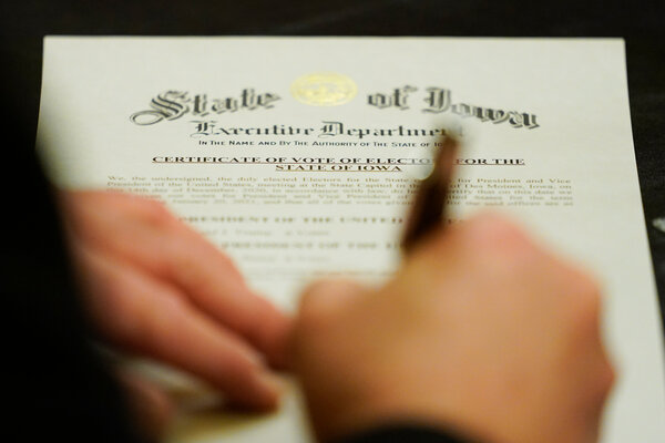 A member of Iowa's Electoral College signing the certificate of vote on Monday at the statehouse in Des Moines.