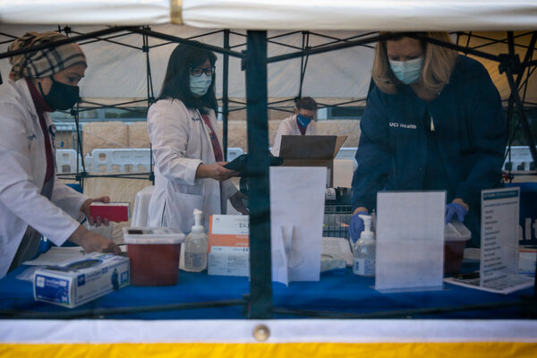 Health care workers at UCI Medical Center in Orange, Calif., setting up supplieson Dec. 16 before administering Pfizer's Covid-19 vaccines to employees.