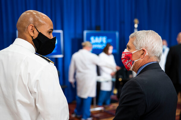 Dr. Jerome Adams, the surgeon general, left, talks with Dr. Anthony Fauci before Dr. Adams received a vaccine on Friday.