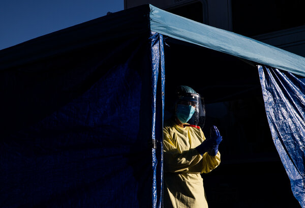 A doctor sanitized between administering Covid-19 tests at a mobile testing unit in Sacramento.