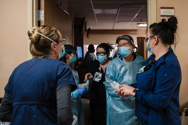 Health care workers by a room where a Covid-19 patient needed to be put on a ventilator in Apple Valley, Calif., last week.