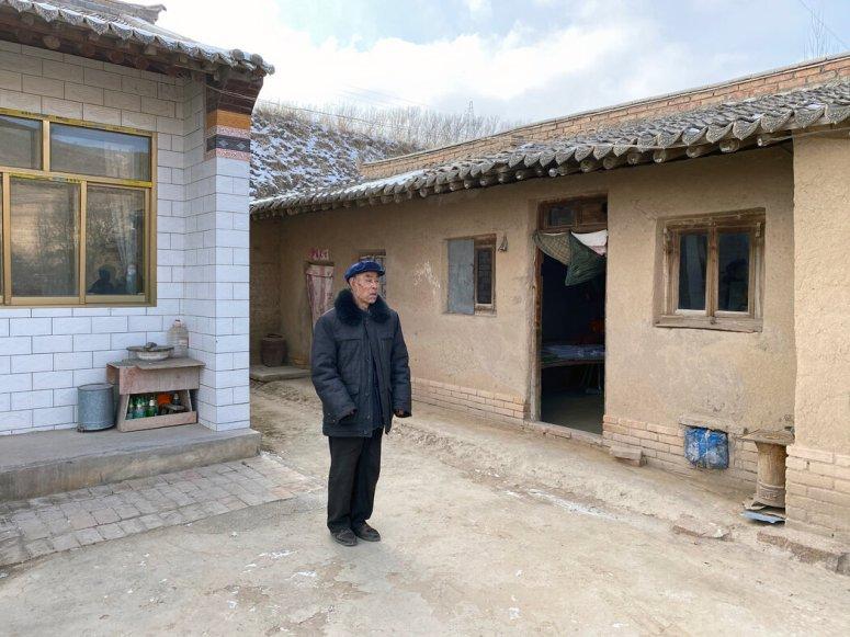 在油坊村,张进鲁在他的老房子和新房子前。