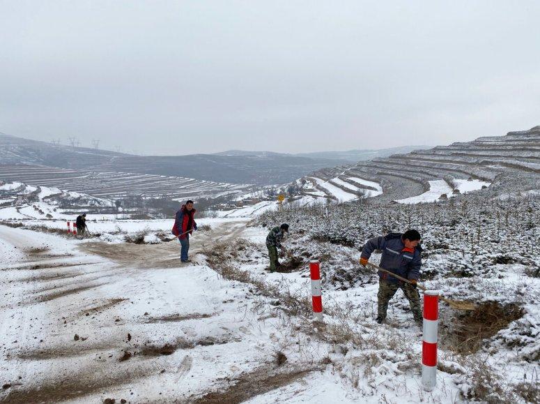 在甘肃省,建筑工人在一条偏远的山区村庄附近将泥土铲到道路上以增加附着力。这是中国扶贫计划的一部分。