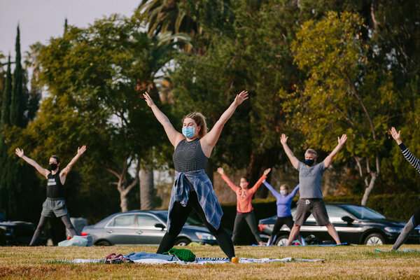 People wearing masks stretched in a vinyasa yoga class Sunday on a lawn at the Hollywood Forever Cemetery in Los Angeles.