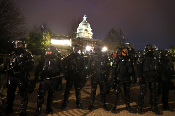 Police officers in riot gear lined up in front of the Capitol after it was overrun by a mob.