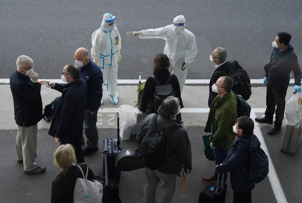 周四,武汉机场,身穿防护服的工作人员迎接世界卫生组织专家组的到来。