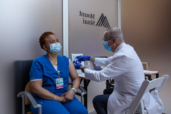 A health care worker receives a Covid-19 vaccine at Mount Sinai hospital in Manhattan last month.