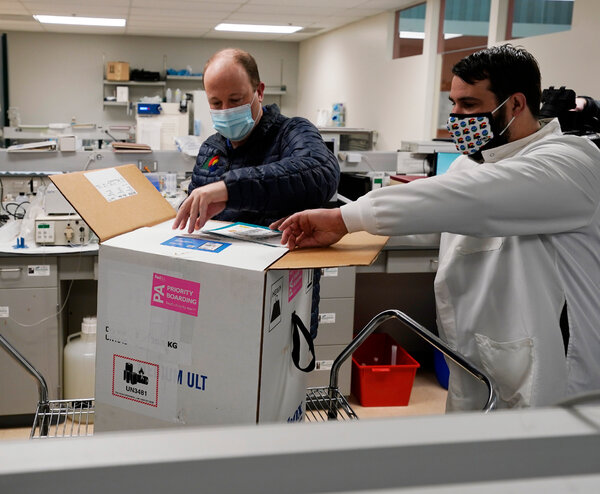Gov. Jared Polis of Colorado, left, opening the state's first shipment of the Covid-19 vaccine on Dec. 14.