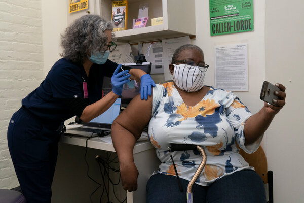 Denise Saylor, right, taking a selfie as Lara Comstack gave her the Modern vaccine at the Callen-Lorde Community Health Center in Manhattan this month.