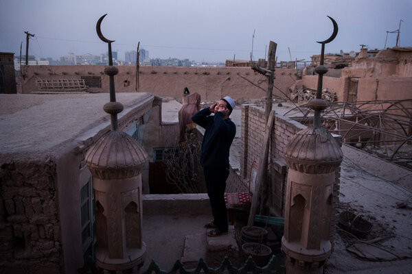 A Uighur muezzin calling the evening prayer from the rooftop of a mosque in Kashgar in 2015.