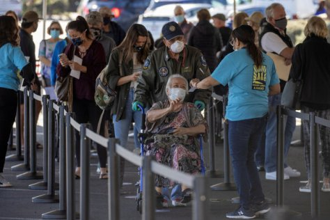 People waiting in line at a super vaccination station set up in an empty department store in Chula Vista.