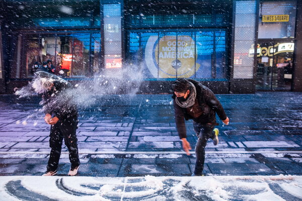 People tossing snow in Times Square on Sunday night. The National Weather Service estimated that one to three inches of snow per hour could fall in the afternoon in New York City on Monday.