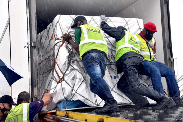 Workers loading South Africa's first coronavirus vaccine doses at OR Tambo airport in Johannesburg on Monday.
