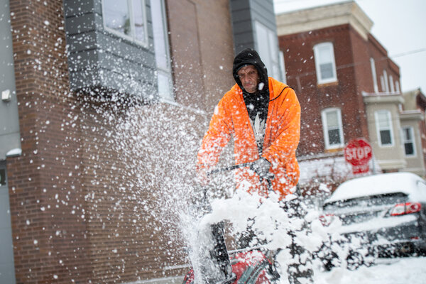 Clearing a sidewalk in Philadelphia on Monday, where 7.7 inches of snow fell near the airport.
