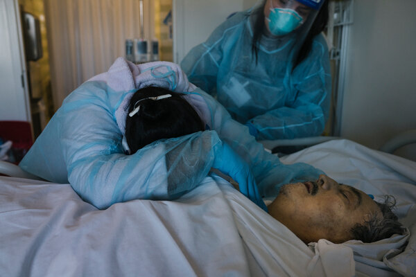 """Carolina Guerrero embracing her husband, Jose Guerrero, after his death in the I.C.U. His daughter, Marisol, shown standing, said, """"This is the unexplainable."""""""