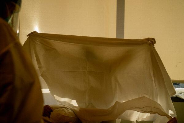 Michelle Goldson, an I.C.U. nurse, covering Emilio Virgen after towel bathing him.