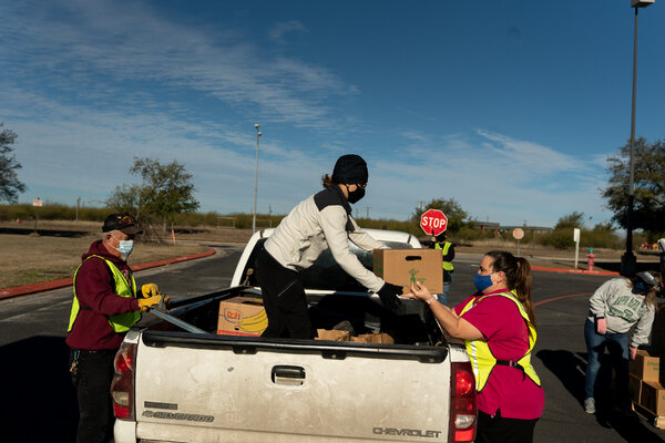 Volunteers distribute donations at a food bank in Pflugerville, Tex., on Wednesday. Emergency aid programs are set to end in March.
