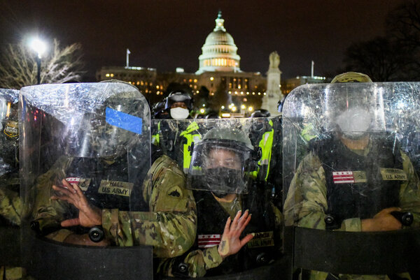 Officers in riot gear lined up in front of the Capitol on Wednesday night after it was overrun by a mob.