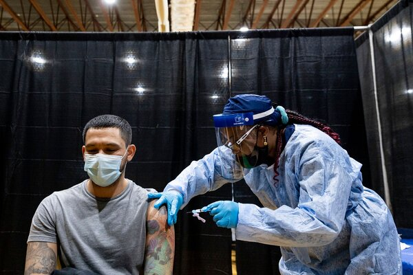 A nurse administering a coronavirus vaccine last Wednesday in Newark. States have each developed their own formulas to determine eligibility for the vaccine.