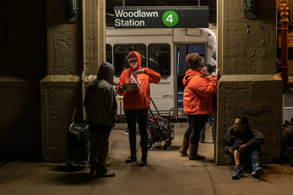 Outreach workers try to sign up homeless people to go to shelters at the Woodlawn subway station in The Bronx.