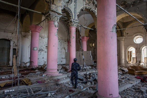 An Iraqi police officer walking through the bombed-out ruins of a centuries-old church that the Islamic State used for its occupation in Mosul's Old City.