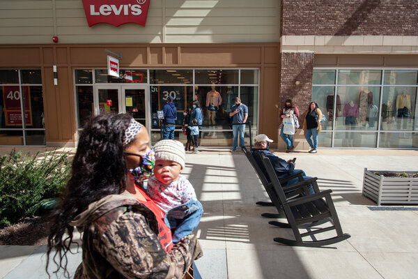 Shoppers wait in line at an outlet mall in Southaven, Miss. on Saturday. Many Americans are set to benefit from the new economic relief plan.