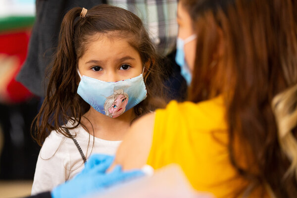 Brittany Siguenza, 5, watching her mother receive a dose of the Moderna vaccine in Revere, Mass., on Friday.