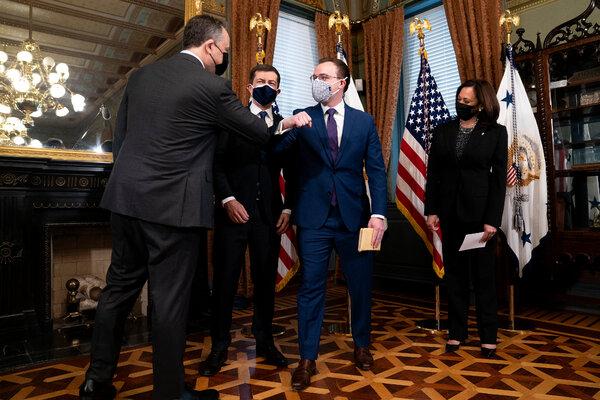 Doug Emhoff, the second gentleman, left, bumps elbows with Chasten Buttigieg,after Pete Buttigieg was sworn in as transportation secretary by Vice President Kamala Harris.