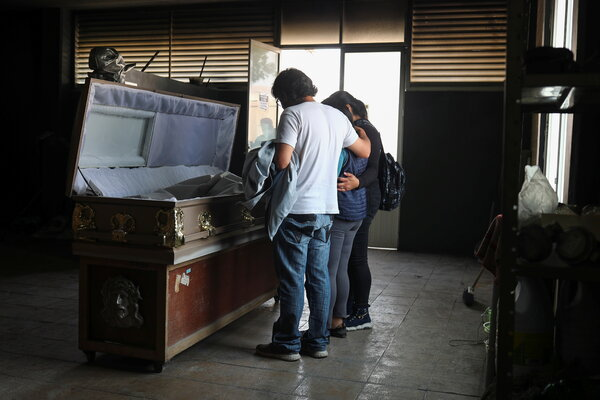 Family members  in Nezahualcóyotl, Mexico, pray beside a loved one who died of the coronavirus this month.