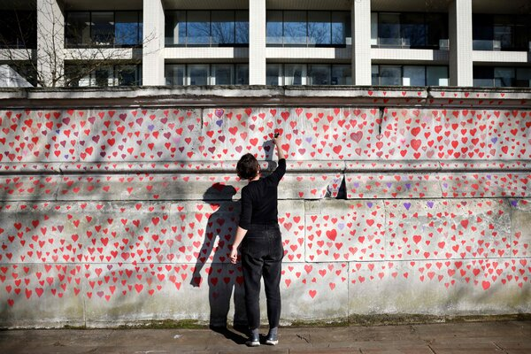 """The display on the southern bank of the Thames in London.""""We keep talking about numbers, but each heart is a person,"""" said Paula Smith, who has been painting the tributes."""