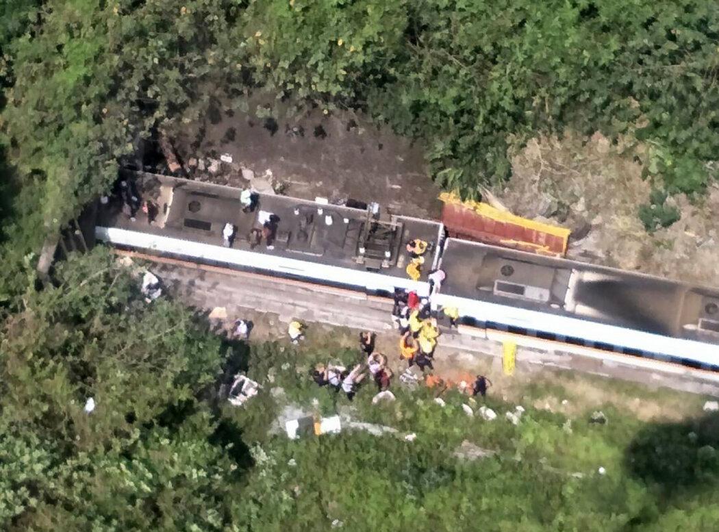 爬下脱轨列车的乘客正在得到帮助。