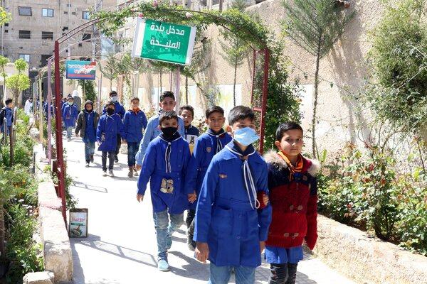 Syrian students walked near their school in a suburb of Damascus on Tuesday. A surge in virus cases has prompted officials to close some schools in the country.