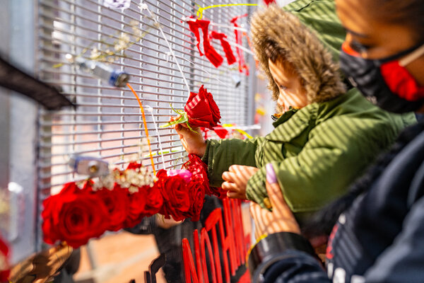 Cayden Totushek affixes roses to a new art piece by Visual Black Justice placed in the courtyard outside of the Hennepin County Government Center.