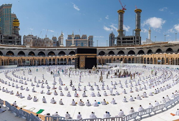 Muslims, maintaining social distances perform Friday prayers as they arrive to perform Umrah, in the Grand Mosque, in the holy city of Mecca, Saudi Arabia, February 26, 2021.