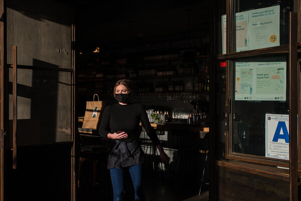 Restaurant workers were some of the hardest hit during the pandemic, and now many are having difficulty getting the vaccine. Here, Alayna Flater walks to a table outside at Zinqué restaurant in downtown San Diego, in January 2021.