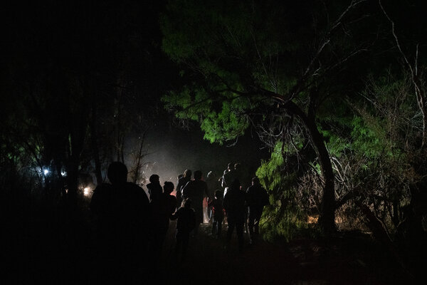 A group of migrants walking up a dirt path after crossing from Mexico into the United States. They were met by pastors from a local church who escorted them to Border Patrol agents for processing.