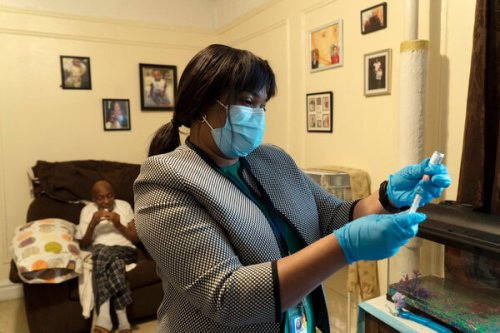 Darcia Bryden-Currie, a nurse, preparing a vaccine for Stephen Elliot at his home in the Bronx, part of an inoculation program for homebound people.