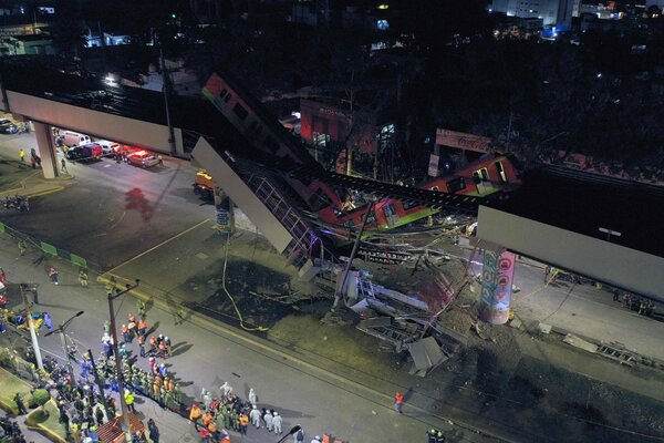 Rescue workers at the site where a train plunged off an overpass that partly collapsed on Monday night in Mexico City.