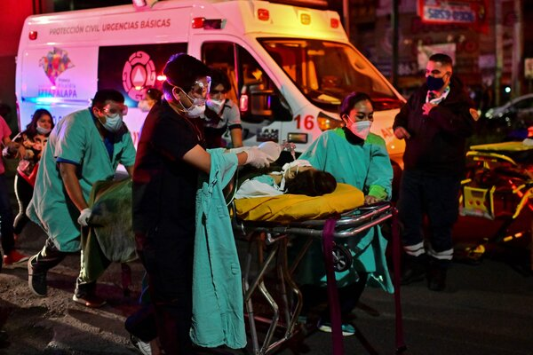 Emergency workers moving an injured person on a stretcher.