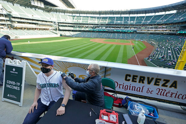 A vaccination clinic before a baseball game in Seattle on Tuesday. Washington is one of many states that is reducing the amount of vaccine doses it requests from the federal government.