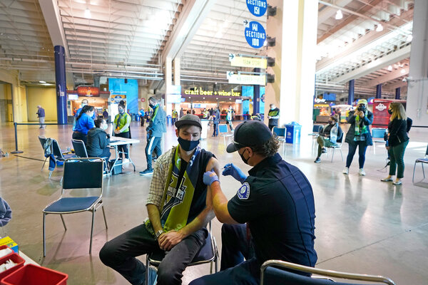Austin Kennedy getting the Johnson & Johnson vaccine at a clinic in a concourse at Lumen Field in Seattle this month.