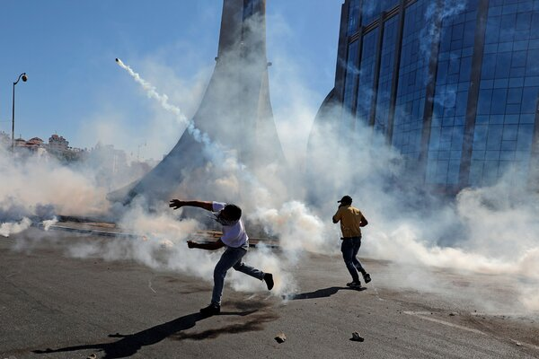 Palestinian demonstrators throw teargas canisters back at Israeli forces during clashes on Friday.