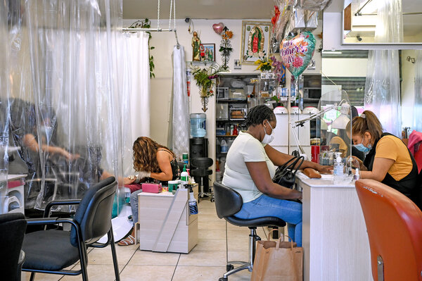 Employees and customers wearing masks inside Jesus Barber Shop Beauty and Nails in the South Bronx.