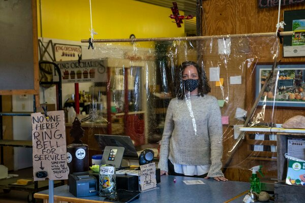 Juliette McAvoy, the V.P. of sales and marketing for King Orchards, behind plastic at the cash registers at their farm stand in Central Lake, Michigan, in mid-May.