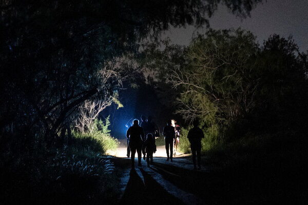 Migrant families seeking asylum in the United States are escorted to the main road to turn themselves in to the U.S. Border Patrol after crossing the Rio Grande near Roma, Texas, on Wednesday.